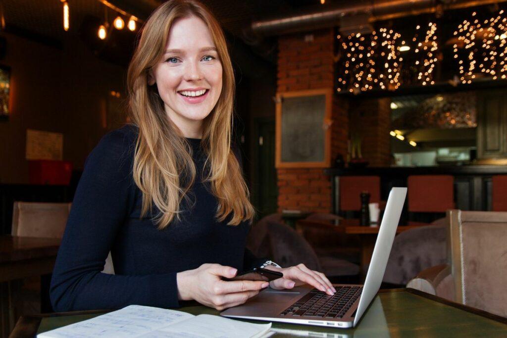 Zufriedene Frau an einem Laptop beim Telefontraining