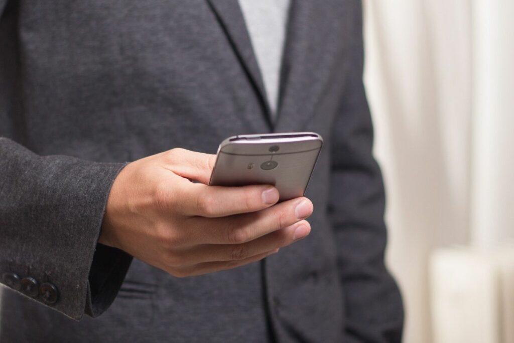 Mann in Anzug hält sein Smartphone beim Telefontraining in der Hand